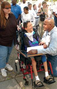 Man talking with boy in wheelchair