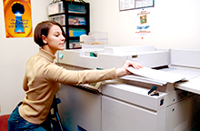 Photo of a young lady with a disability using a copy machine.