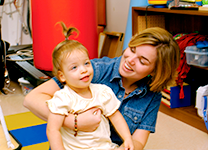 Photo of a young girl with a developmental disability being held by her teacher.