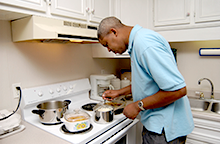 Photo of a man with a disability cooking dinner in his own residence.