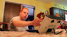 Photo of Michael, a client of Disability Rights Florida, using his assistive technology device.